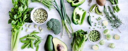 Photo pour Propagation saine des légumes verts sur fond blanc rustique à partir des frais généraux, brocoli, céleri, avocat, choux de brosse, kiwi, poivre, pois, haricots, laitue , - image libre de droit