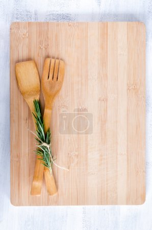 Photo for Wooden utensils tied with rosemary on bamboo chopping board from overhead, food background - Royalty Free Image