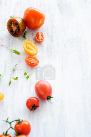 tomatoes on rustic background with leaves
