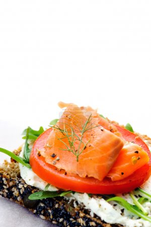 Photo for Healthy lunch with smoked salmon, salad and a fresh cheese spread on a slice of seeded bread - Royalty Free Image