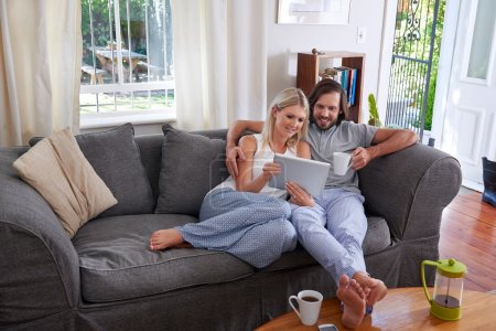 Photo for Smiling couple with tablet computer and coffee mugs on sofa couch at home - Royalty Free Image