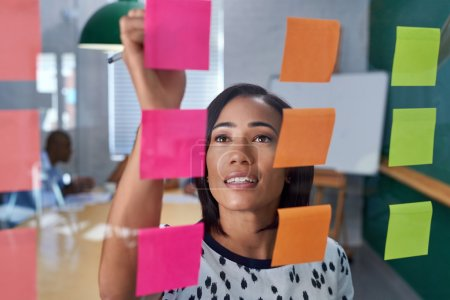 businesswoman writing on post it note
