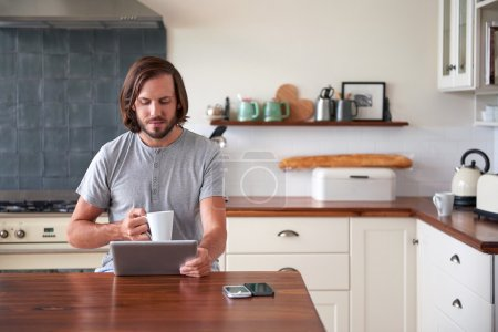 man enjoying morning coffee with tablet computer
