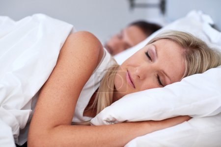 Photo for Peaceful young couple sleeping comfortably with alarm clock in bed at home - Royalty Free Image