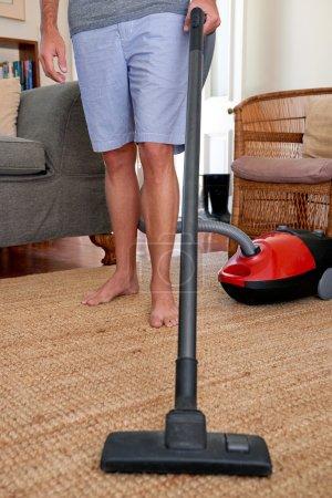 Man at home vacuuming the carpets
