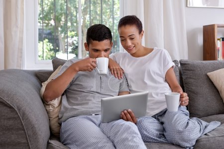 couple having coffee and looking at tablet