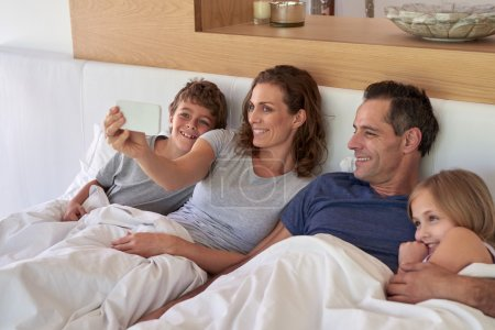 Photo for Pretty mature smiling mom taking a family selfie using a mobile smartphone phone of husband and kids in bed - Royalty Free Image
