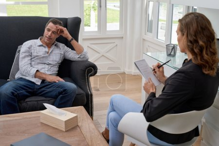 Photo pour Psychologue femme consultant homme mûr pendant la séance de thérapie - image libre de droit
