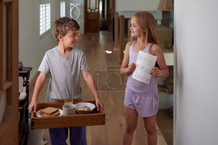 Boy and girl carrying breakfast tray