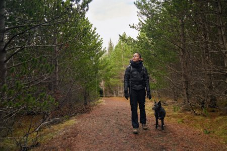 Photo for Happy active lifestyle woman walking hiking trekking in forest woods with best friend companion pet dog - Royalty Free Image