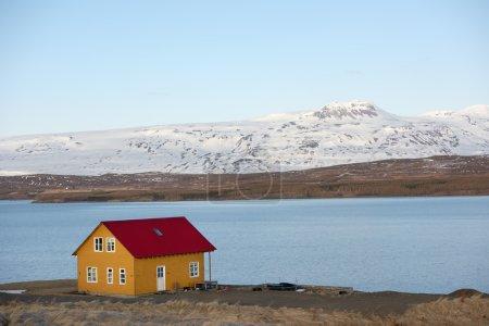 Photo pour Maison de campagne pittoresque en iceland, surplombant le fjord d'eau et les montagnes enneigées au loin - image libre de droit