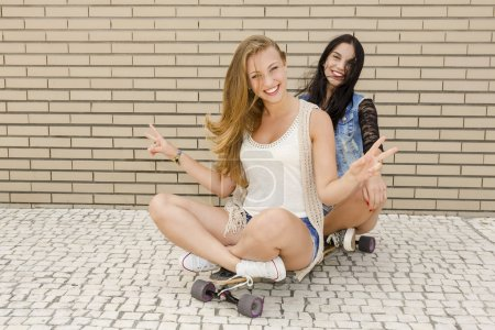 Happy girlfriends having fun with a skateboard