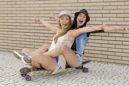 Girlfriends having fun with a skateboard