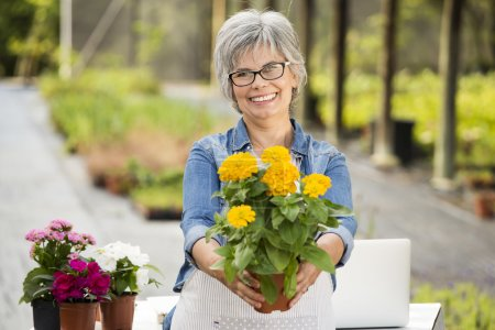 Mature woman holding flowers on her hands