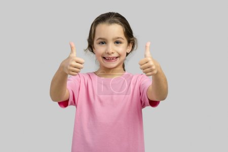 Photo for Studio portrait of a beautiful little girl with thumbs up - Royalty Free Image