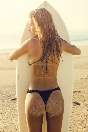 Woman embracing her surfboard