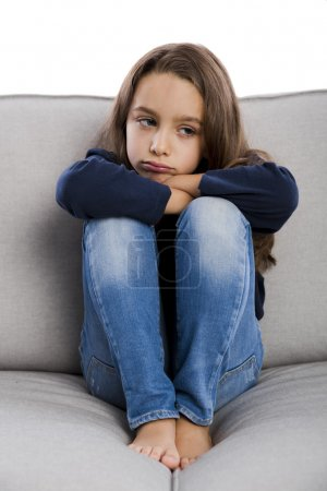 Upset little girl sitting on a couch
