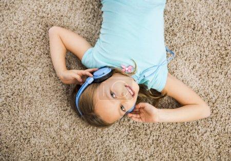 Little girl listen music with headphones