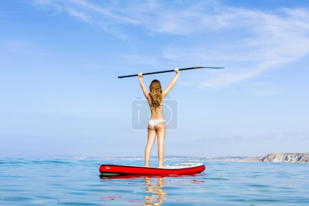 Happy woman learning paddle-surf
