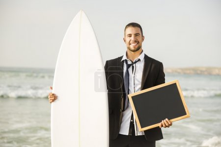 Photo for Businessman holding a chalkboard and his surfboard on beach. Concept about a man starting a new life. - Royalty Free Image