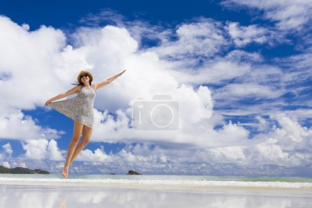 Beautiful woman jumping at the beach