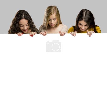 girls holding cardboard