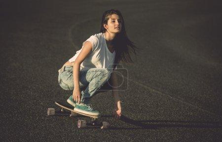 Photo pour Jeune femme faisant de descente avec une planche à roulettes - image libre de droit