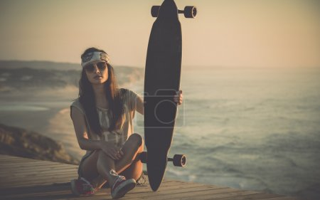 Photo for Beautiful fashion skater girl posing with  a skate board - Royalty Free Image