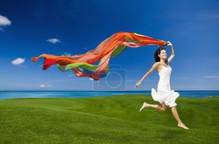 Photo pour Belle femme sautant sur une prairie verte avec des tissus colorés - image libre de droit