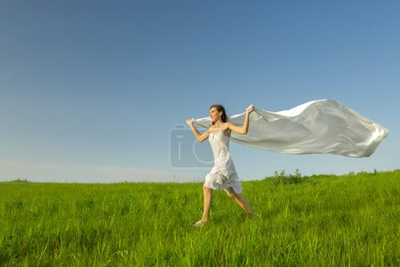 Photo for Young beautiful woman running while holding a white tissue - Royalty Free Image