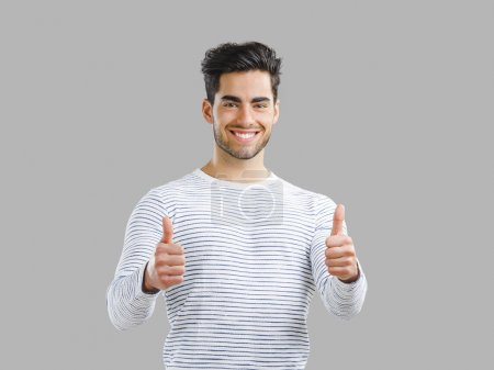 Photo for Portrait of handsome young man with thumbs up,  isolated over a gray background - Royalty Free Image