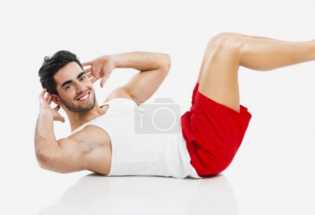 Photo for Athletic young man doing ABS, isolated over a gray background - Royalty Free Image