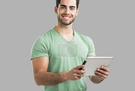 Photo for Handsome young man working with a tablet, isolated over gray background - Royalty Free Image