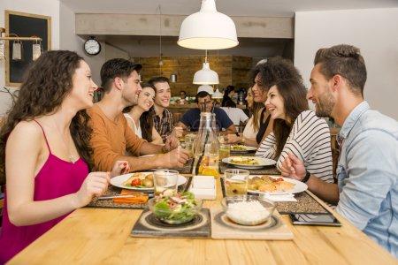Photo pour Groupe multi-ethnique de joyeux amis déjeunant et s'amuser au restaurant - image libre de droit