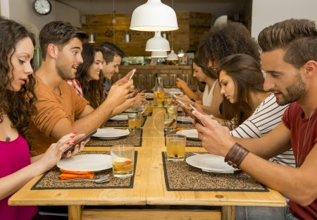 Photo for Group of friends at a restaurant with all people on the table occupied with cellphones - Royalty Free Image