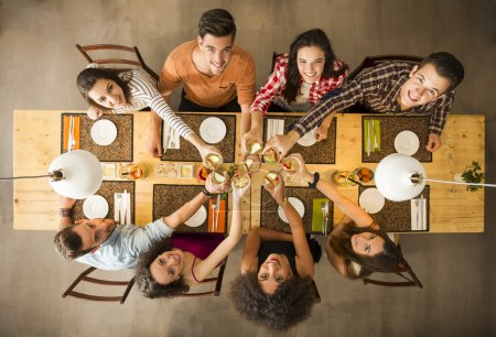 Photo for Group of people toasting and looking happy at a restaurant - Royalty Free Image