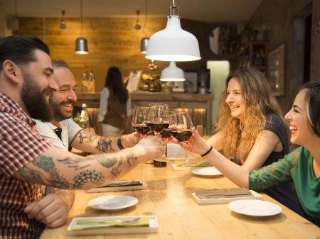 Photo pour Groupe d'amis de grillage et passer un bon moment au restaurant - image libre de droit