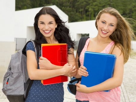 teenage students holding notebooks and smiling