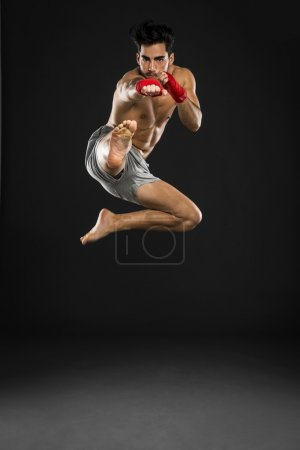 athlete in boxing bandages jumping and kicking