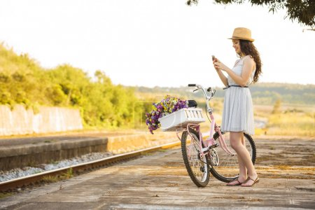 Photo for A beautiful young woman with her bicycle full of wildflowers - Royalty Free Image