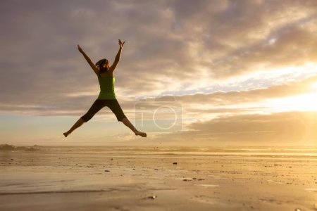 Photo for Silhouette of a woman jumping  on a the beach at the sunset - Royalty Free Image