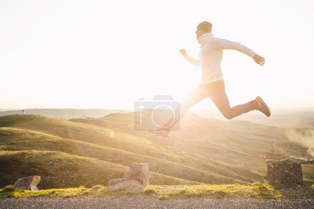 Photo for Man jumping over precipice between two stones on mountains at sunset - Royalty Free Image