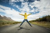 Woman jumping on a beautiful road