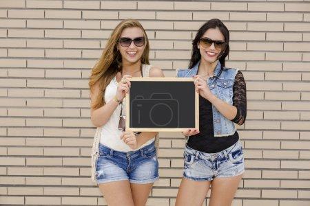 Teenage friends holding a chalkboard