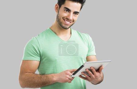 Photo pour Beau jeune homme travaillant avec une tablette, isolé sur fond gris - image libre de droit