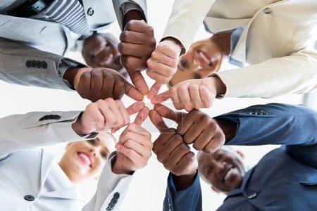 Photo pour Groupe de gens d'affaires joyeux en cercle regardant vers le bas - image libre de droit