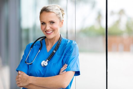 Photo for Cheerful female medical worker with arms folded - Royalty Free Image