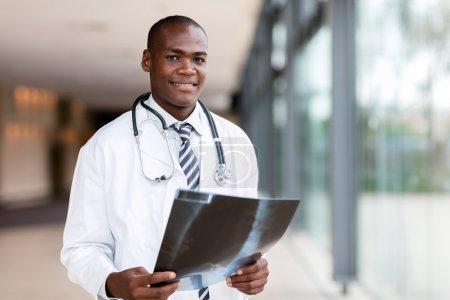 Photo pour Docteur en médecine africaine heureux en regardant des films radiographiques - image libre de droit