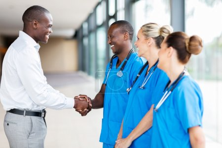 medical representative handshaking with doctors in hospital