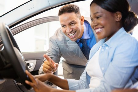 salesman showing car to female customer